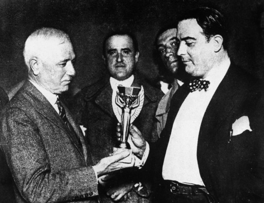 Jules Rimet (left), president of FIFA (Federation Internationale de Football), presents the first World Cup trophy to Dr. Paul Jude, president of the Uruguayan Football Association, after Uruguay's victory over Argentina, 30 July 1930.