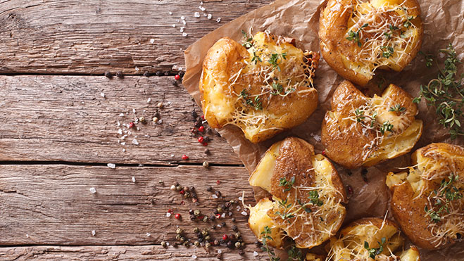 Rustic food: hot baked new potato with thyme on the table. horiz
