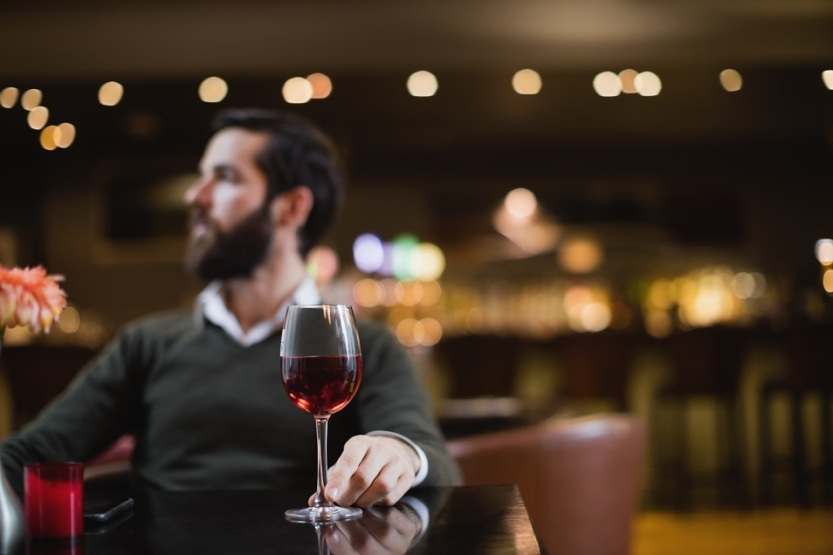 Man sitting with glass of wine in bar