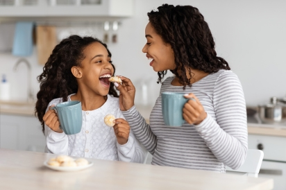 Happy black lady mom feeding her kid with cookies, sitting on kitchen and having snack together. Happy african american mother and daughter enjoying buscuits with tea at home, copy space
